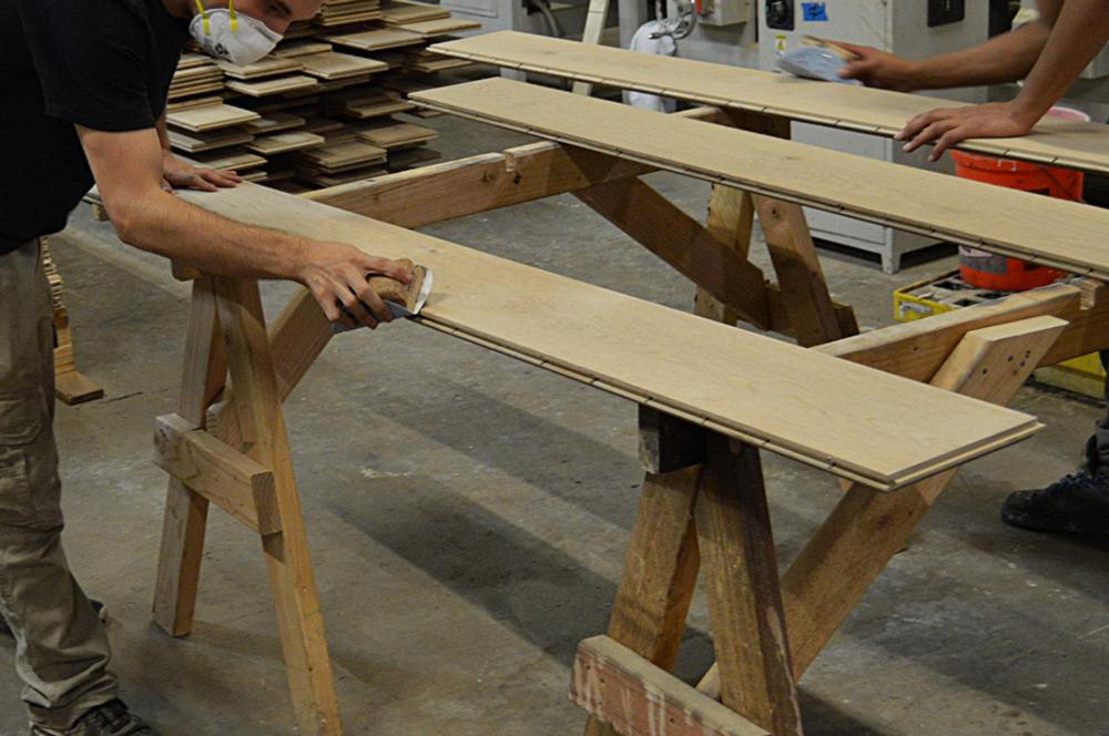 worker applying hardwood wax at finish mill